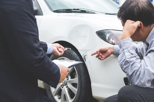 Man and insurer inspecting car accident damage